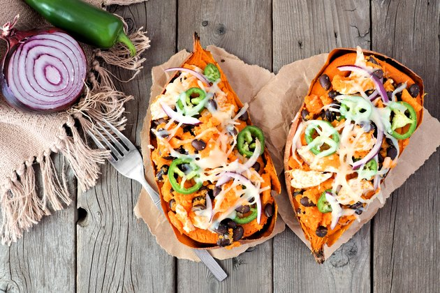 Baked, stuffed sweet potatoes,  above view on rustic wood