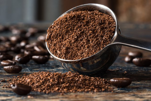 Close-Up Of Ground Coffee In Measuring Cup On Table