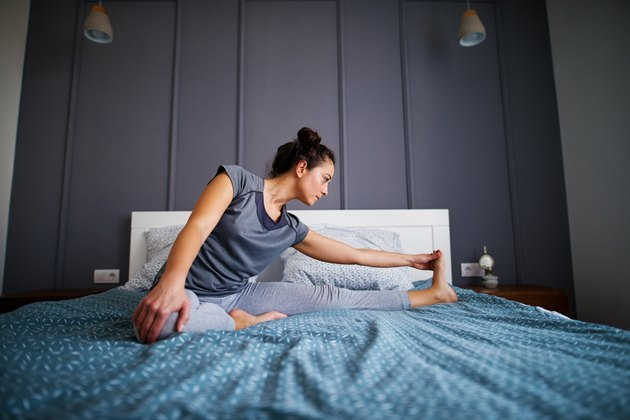 Attractive shape sporty middle aged woman doing seated yoga poses Janu Sirsasana or Head-to-Knee Forward Bend on the bed before sleeping.