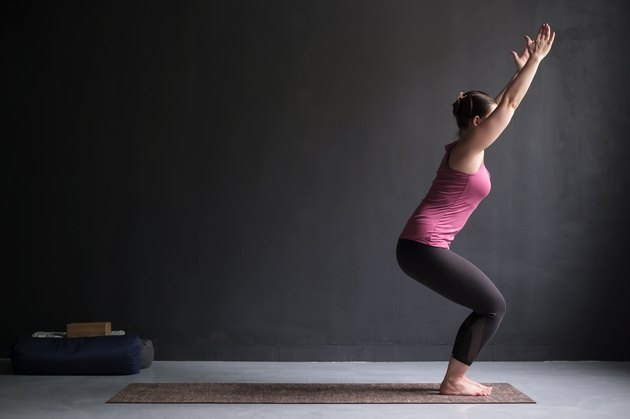Woman practicing yoga, doing Chair exercise, Utkatasana pose, working out.