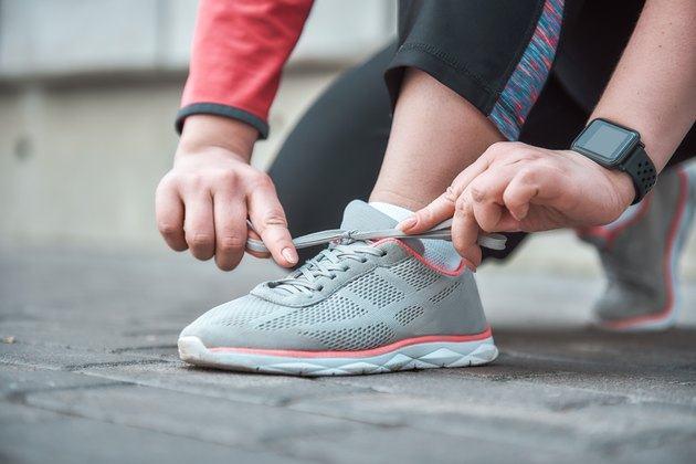 Cropped image of a woman in sports clothing tying shoelace while standing outdoors
