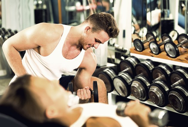 well trained man training hands using heavy weight dumbbells in