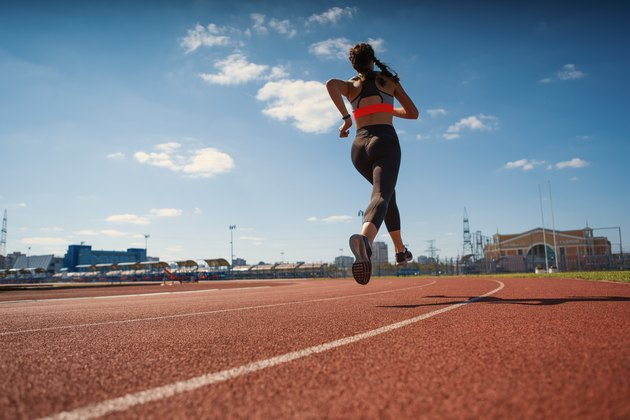 From below back view of female teen athlete in sportswear running on track at stadium on summer day