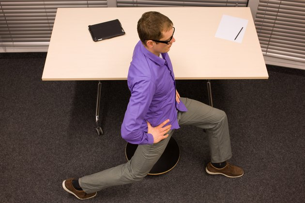 man on pneumatic stool having break for exercise in workplace