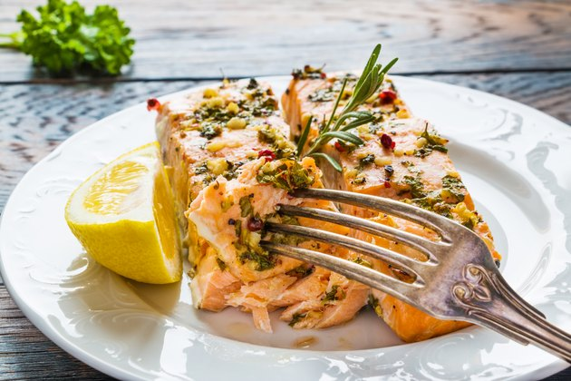 Salmon roasted in an oven with a butter, parsley and garlic. Portion of cooked fish and fresh lemon on a white plate on the wooden table.