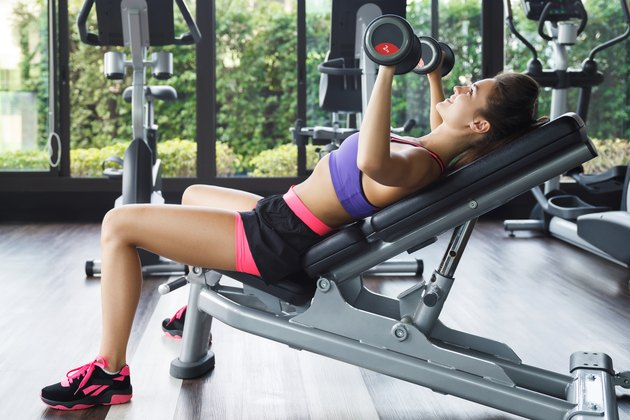 Woman performing incline bench press.