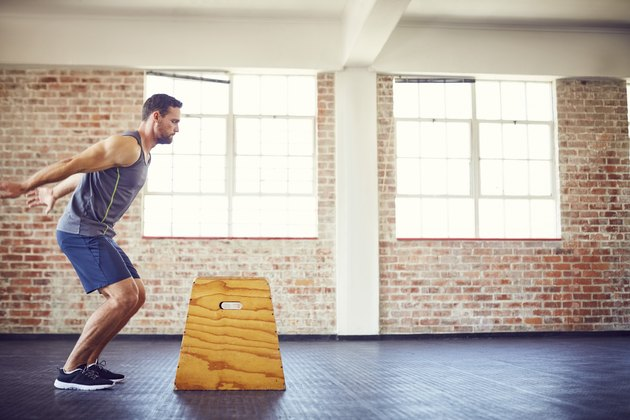Male athlete doing box jumping at gym to build strength for runners