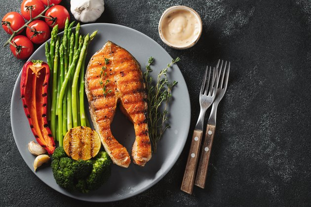 Tasty and healthy salmon steak with asparagus, broccoli and red pepper on a gray plate. Diet food on a dark background with copy space. Top view. Flat lay