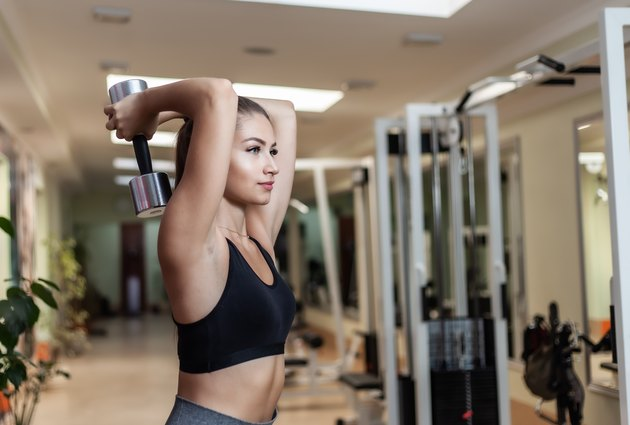 Woman performing overhead dumbbell extension.