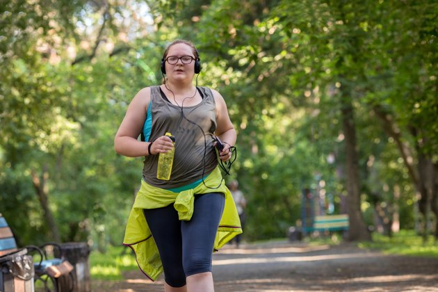 Woman running through the park listening to music