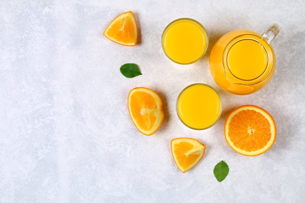 Glass bottles, glasses and a pitcher of fresh orange juice with slices of orange and yellow tubes on a light gray table. Top view. Flat Lay.