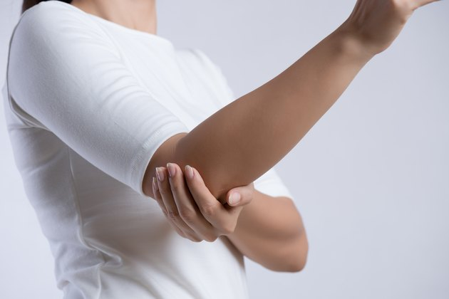 Closeup female's elbow. Arm pain and injury. Health care and medical concept.