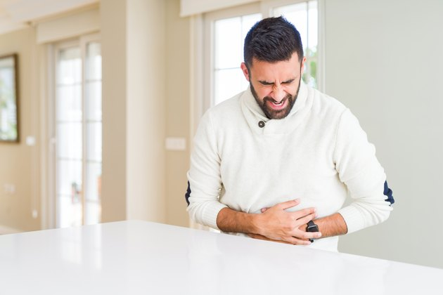 Handsome hispanic man wearing casual white sweater at home with hand on stomach because nausea, painful disease feeling unwell. Ache concept.