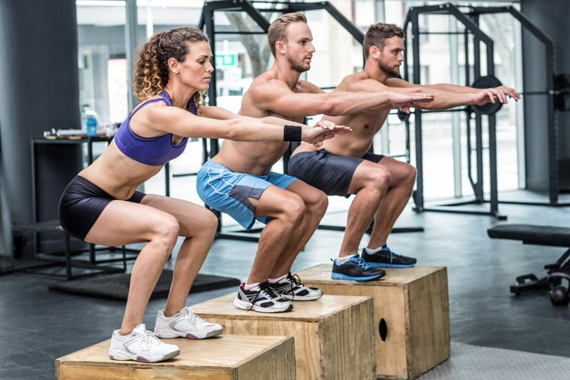 Three muscular athletes doing jumping squats