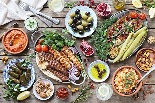 Middle eastern, arabic or mediterranean dinner table with grilled lamb kebab, chicken skewers  with roasted vegetables and appetizers variety serving on rustic outdoor table.