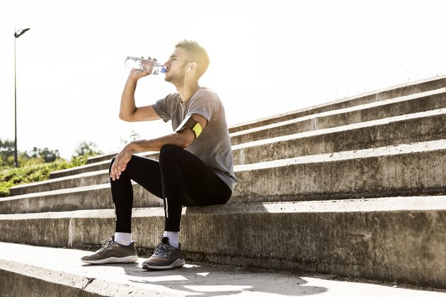 Athlete resting and re-hydrating with water