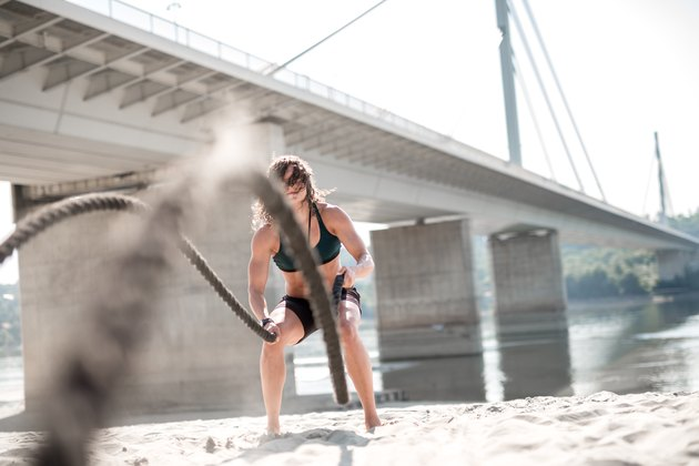 Women athlete doing workout with battle rope