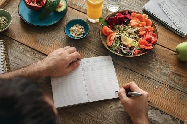 A man on the CICO diet writing in a food journal