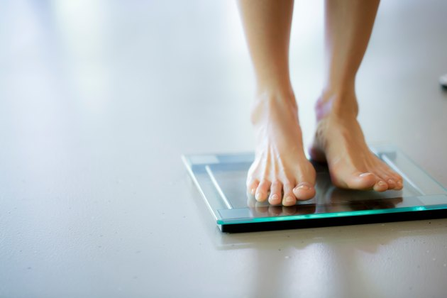 Close view of a person's feet standing on a clear bathroom scale