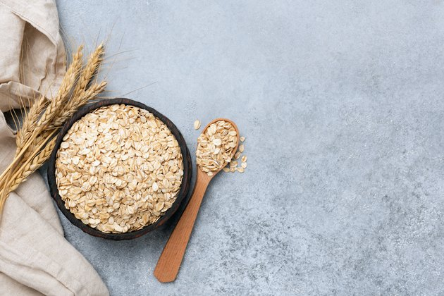 Bowl of rolled oats (oat flakes) on concrete background