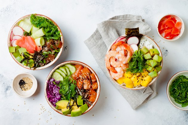 Hawaiian salmon, tuna and shrimp poke bowls with seaweed, avocado, mango, pickled ginger, sesame seeds. Top view, overhead, flat lay