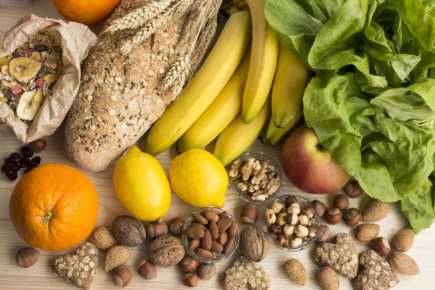 bananas, lettuce, lemons, nuts and other healthy foods on wooden table