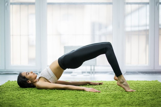 Young sporty woman practicing yoga, doing dvi pada pithasana exercise, Glute Bridge pose, working out, wearing sportswear at home