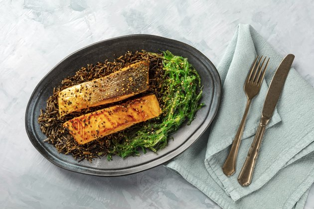 Grilled salmon with sesame seeds, wakame seaweed and wild rice, overhead shot