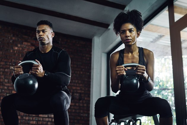 man and woman holding kettlebells doing muscle-building goblet squats