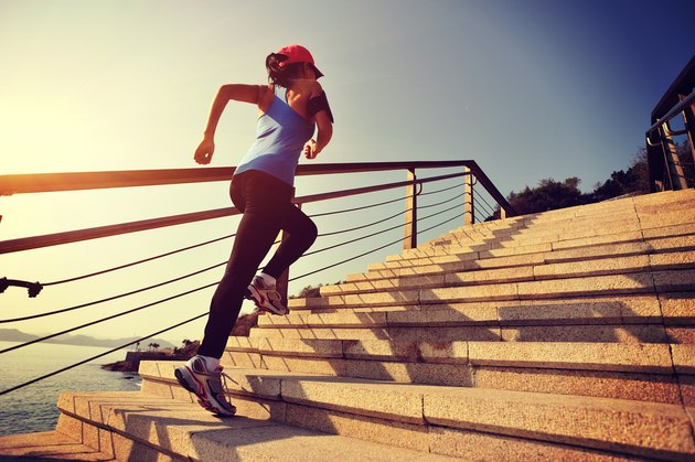 Sportswoman running up on stone stairs