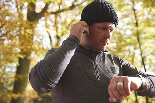 Man On Run Checking Fitness Tracker And Putting In Earphones