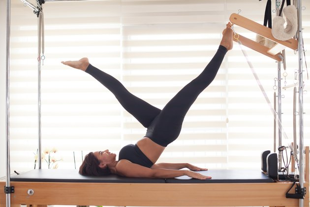 Woman doing workout on Pilates reformer at home