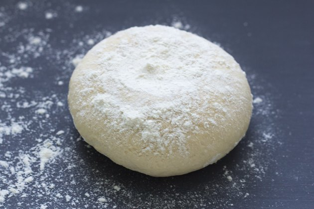 fresh raw baking dough sprinkled with flour on a dark background
