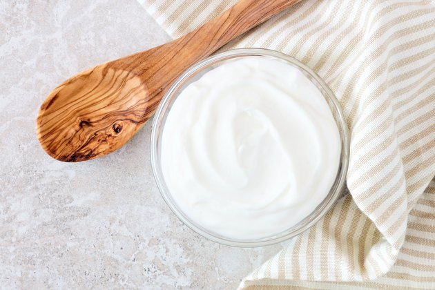 Greek yogurt, with cloth and spoon on white marble