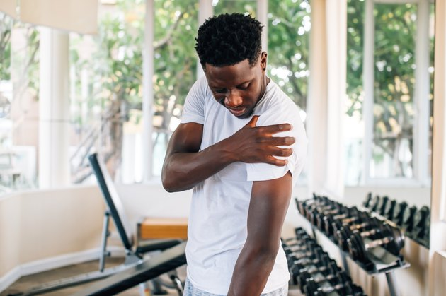Sportsman holding shoulder that pops and cracks in gym