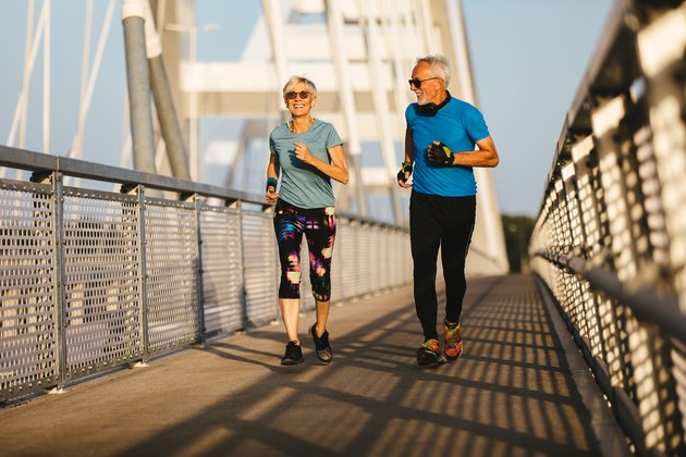 Senior couple jogging together over the bridge