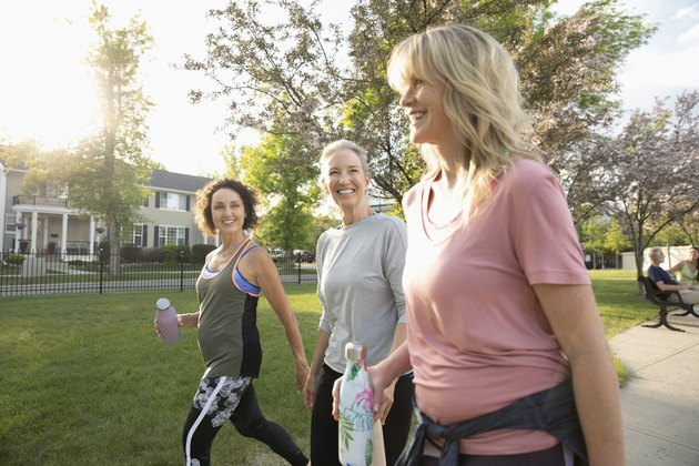 Smiling senior women walking, exercising in sunny park