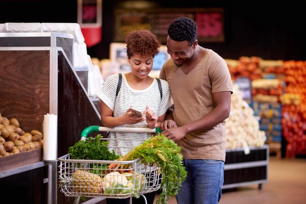 Man and woman in grocery store looking at phone ensuring they stay on track with their shopping budget