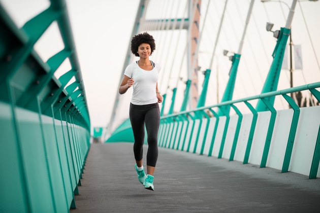 Teen girl exercising on bridge