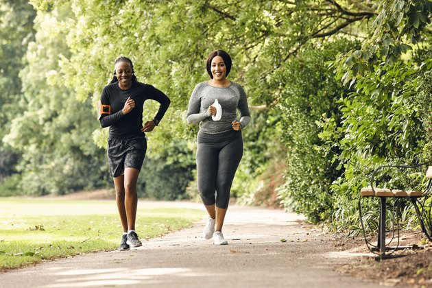 two women running in the park for partner workout