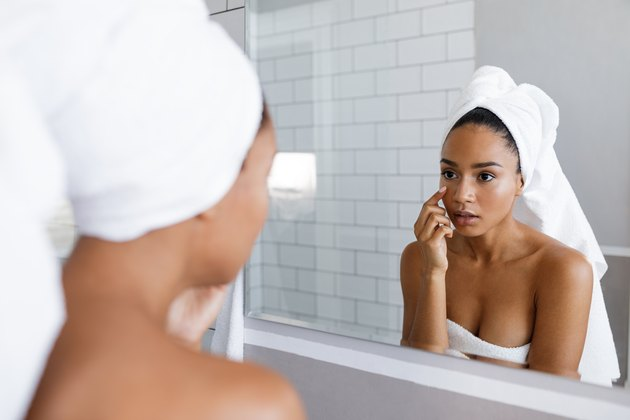 Close up shot of an attractive young woman inspecting her skin, standing in front of the bathroom mirror
