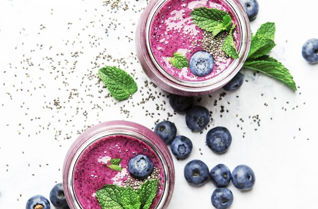 Purple homemade smoothie with blueberries, chia seeds and mint leaves in glass jars on white background, flat lay, top view