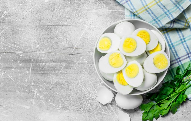 Boiled eggs in a bowl with parsley.