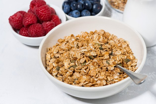 muesli and fresh berries on white table, closeup
