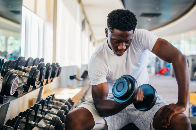 Young man sitting and lifting a dumbbell with the rack at gym