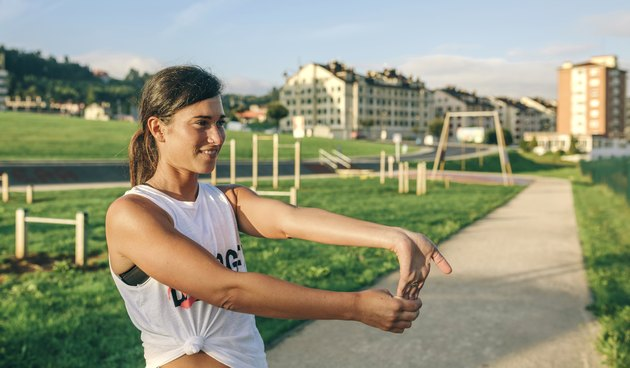 Woman looking away while stretching wrist at park