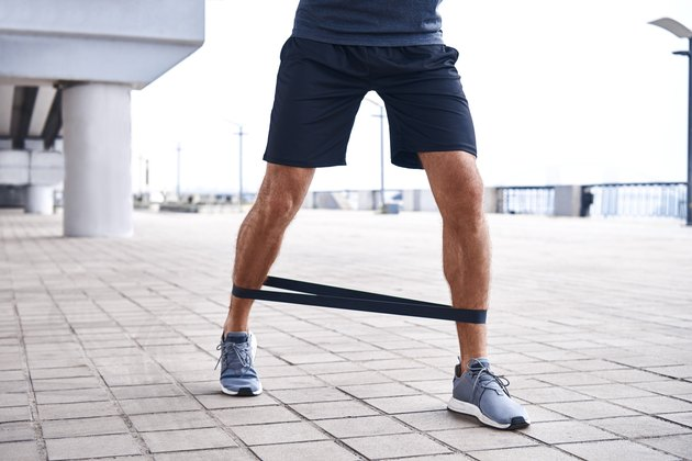 Close-up of young sportive man uses resistance band for exercising outdoors