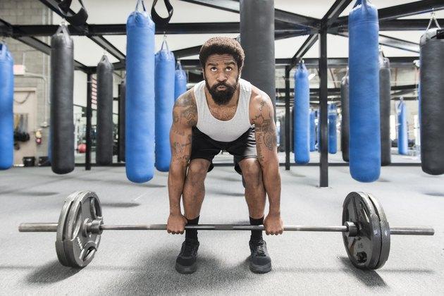 Black man lifting barbell in gymnasium