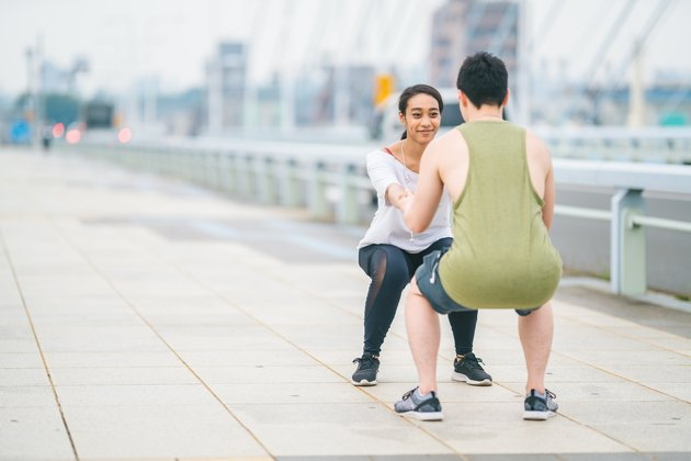Multi-ethnic young happy couple training in city