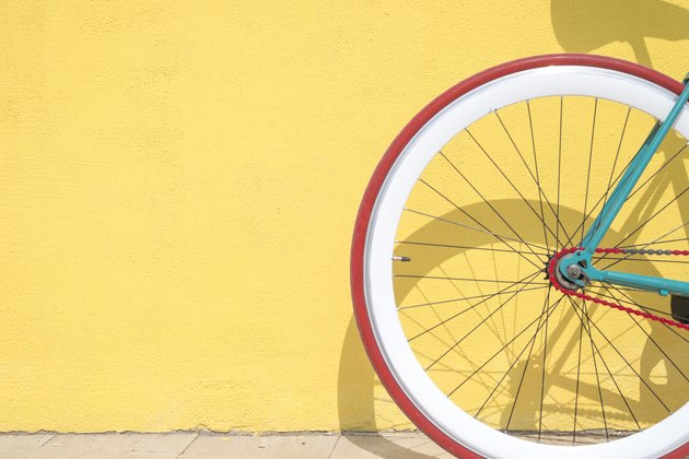 Close-Up Of Bicycle Parked By Yellow Wall with Red Tire